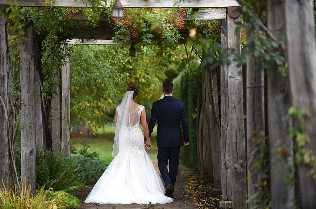 Beautifully romantic wedding picture of a Bride and groom at Great Fosters in Surrey walking hand in hand through an atmospheric old wooden beamed arbour