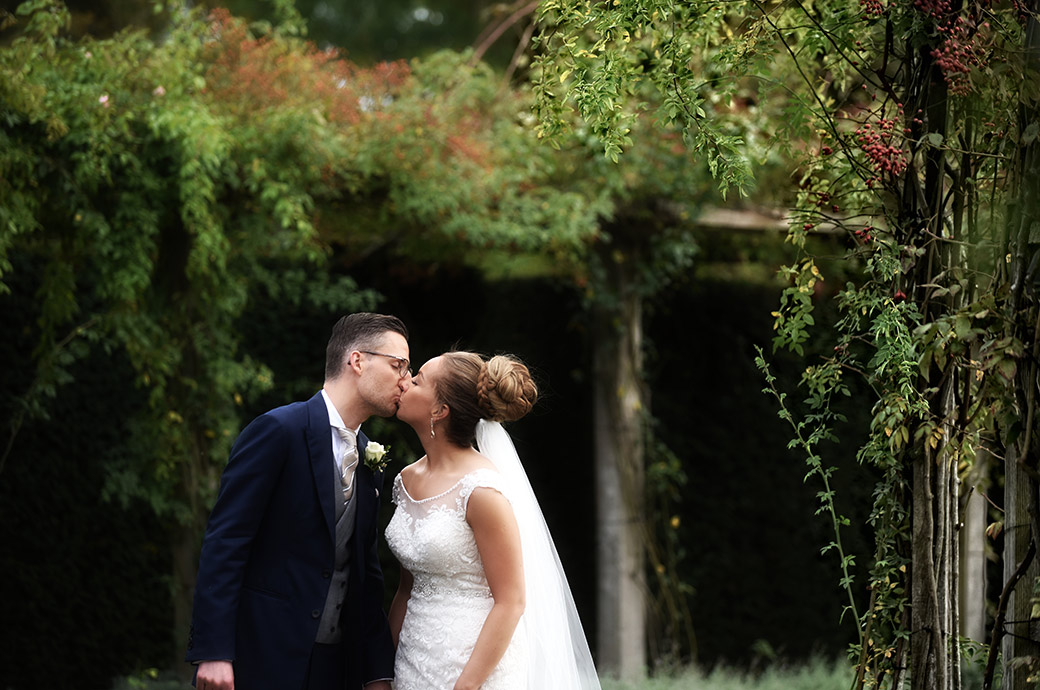 Couple romantically kiss in the sunken rose garden captured in this wedding photograph taken at the wonderful Surrey hotel and event venue Great Fosters in Egham