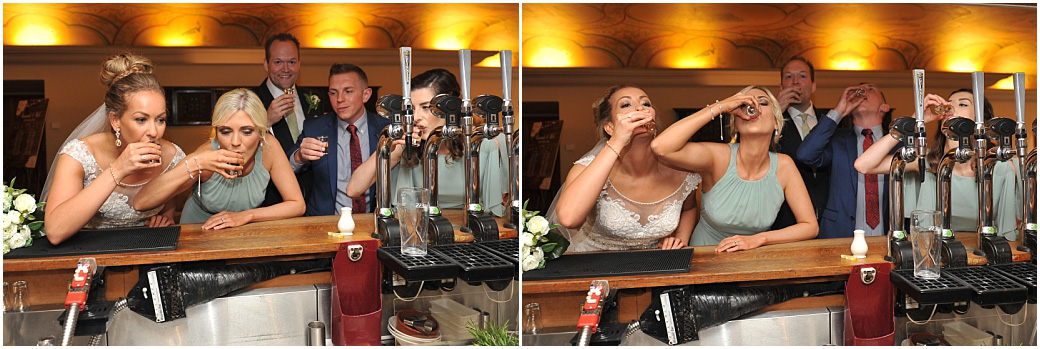 The Bride and the wedding party at the wonderful Surrey wedding venue Great Fosters in Egham take a quick shot at the bar in the Painted Hall before entering The Orangery