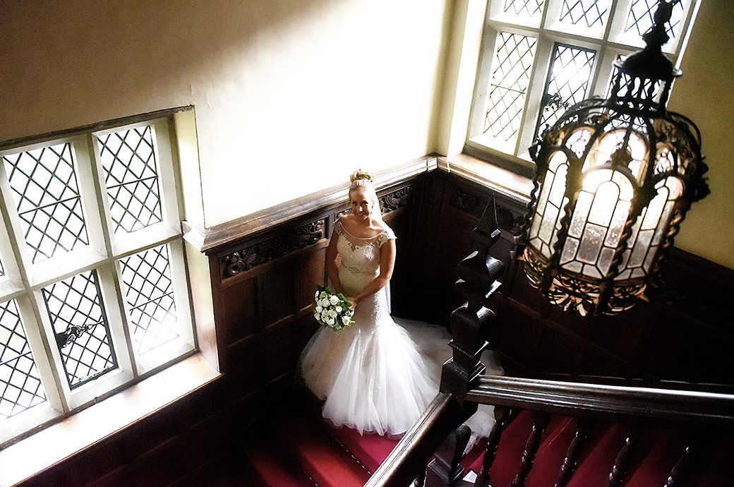 Beautiful excited Bride standing on the stairs at Great Fosters in Egham Surrey on route from the Nursery Suite to the Orangery for her wedding ceremony