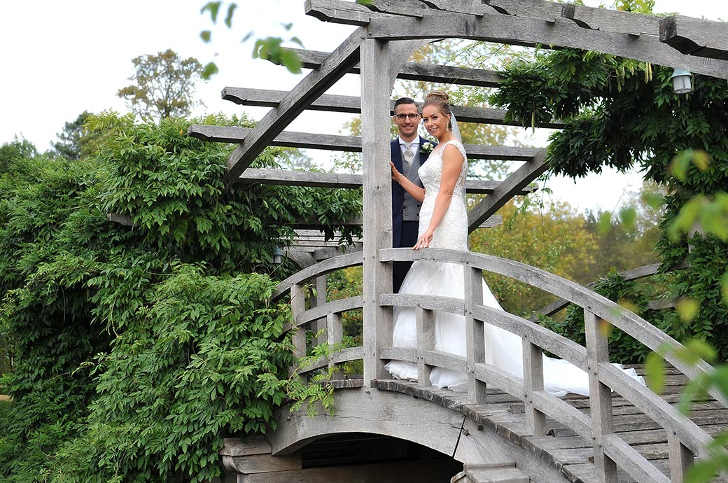 Lovely smiling Bride and her groom captured at the stunning Surrey wedding venue Great Fosters Egham as they take a moment to stop on the charming wooden Japanese Bridge