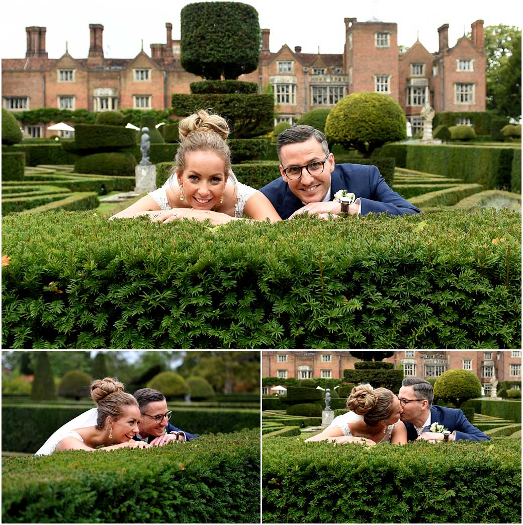 Happy smiling Bride and groom captured having fun at the wonderful Surrey wedding venue Great Fosters where they are leaning over a hedge and kissing in the formal Parterre garden