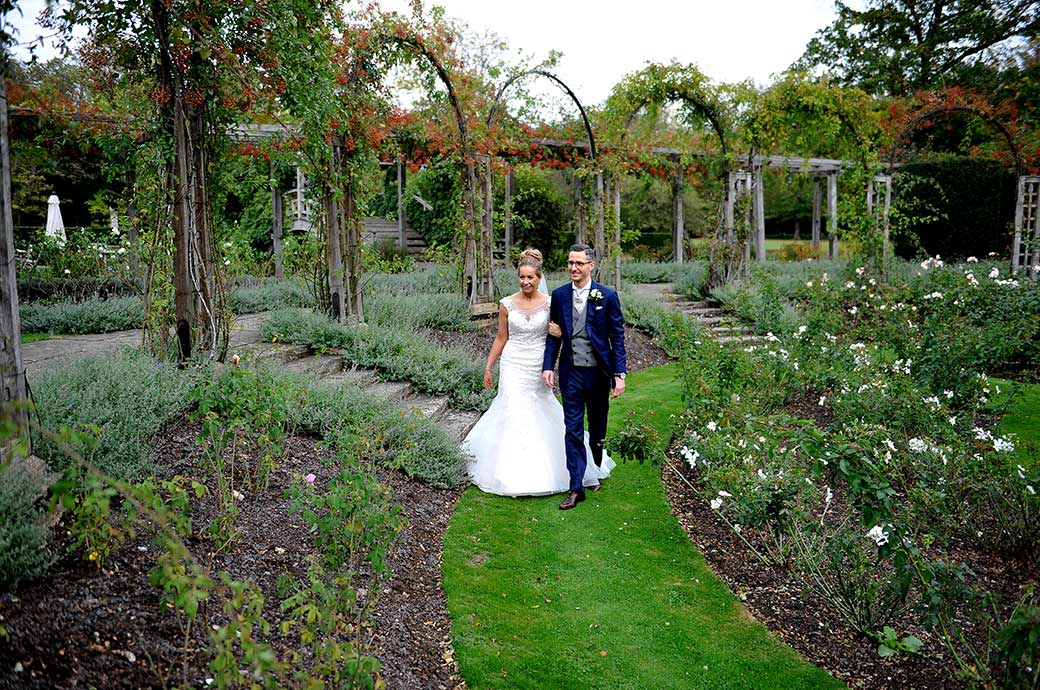 Relaxed and very happy couple walking through the wonderfully tranquil and pretty sunken rose garden at the stunning Surrey wedding venue Great Fosters