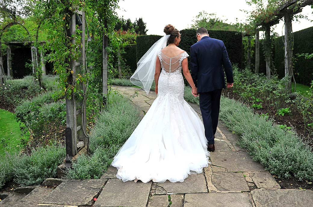 Romantic wedding picture taken from behind as a couple walk along the path in the sunken rose garden at the fabulous Great Fosters wedding venue in Egham Surrey