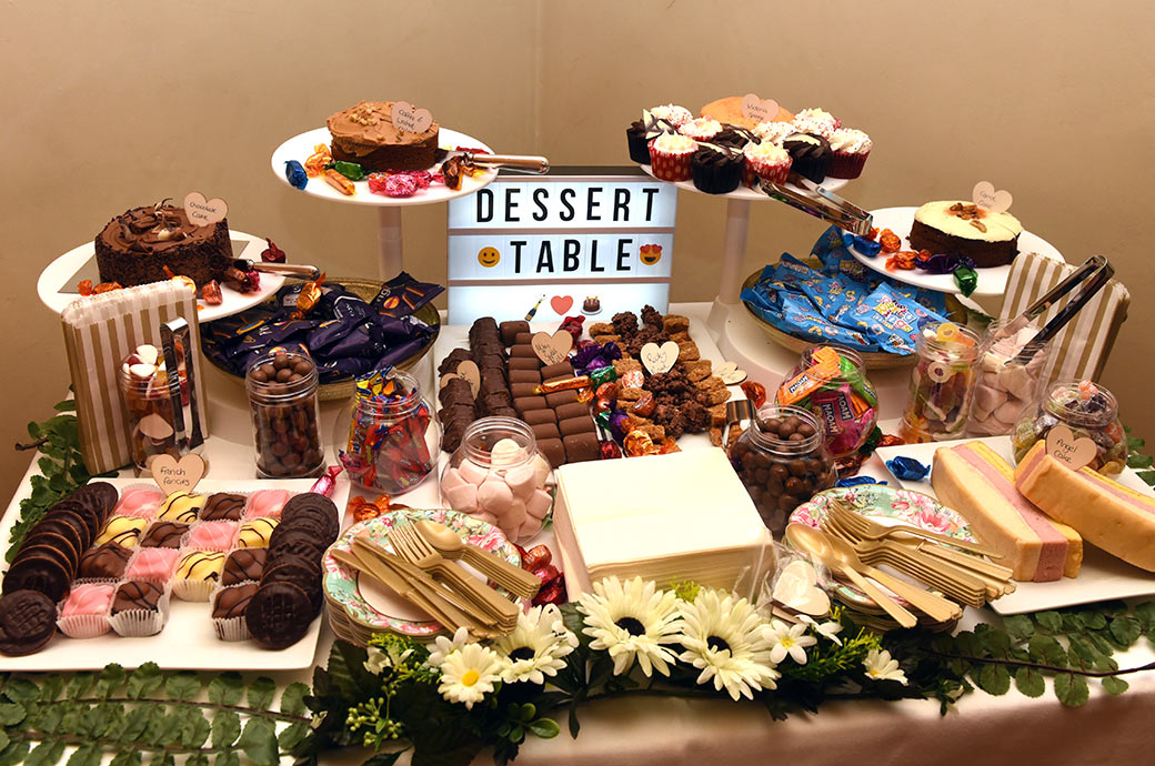 Picture of a colourful Dessert Table full of very sweet chocolaty cakes and sweets for guests after the wedding breakfast in the Painted Hall at Great Fosters in Egham Surrey