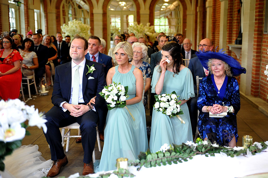 Attentive and emotional front row look on at the start of the marriage ceremony in The Orangery at the fabulous Great Fosters Surrey wedding venue