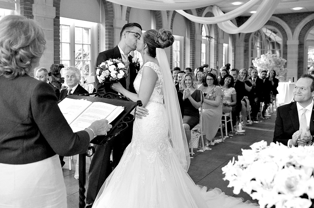 Bride and groom in The Orangery at Surrey wedding venue Great Fosters Egham seal their marriage with a lovely romantic wedding kiss