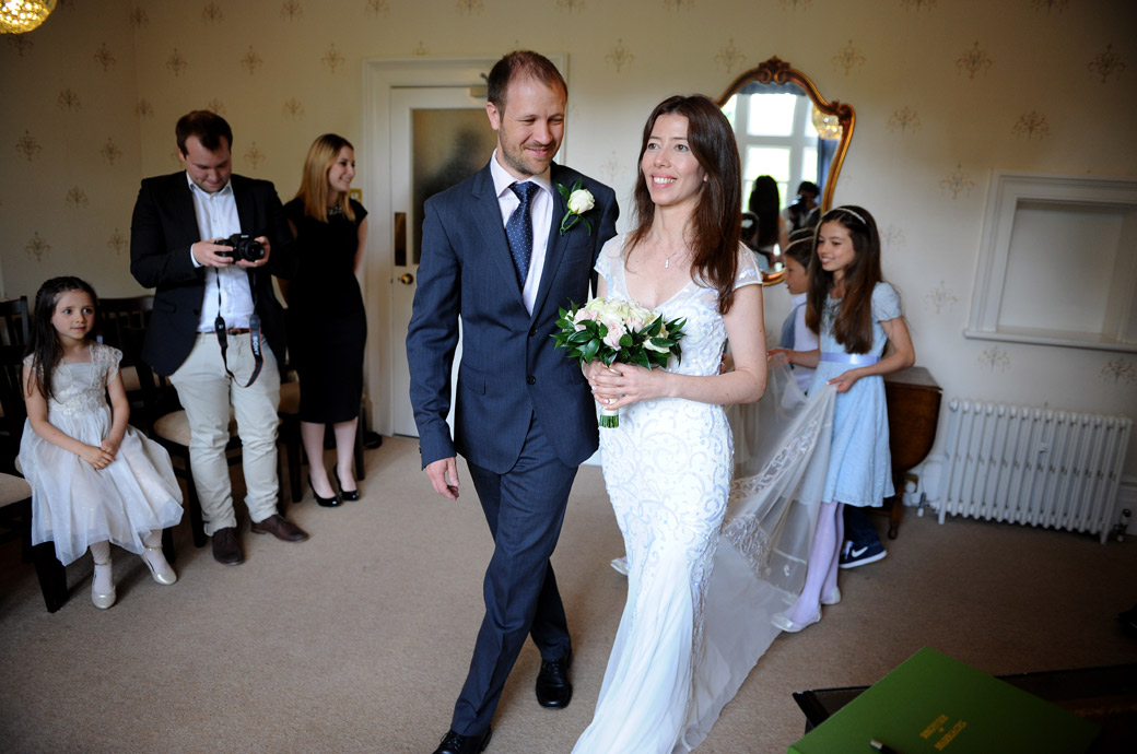 Bride and groom walk into the smaller marriage room at Guildford Register Office in Artington House Surrey followed by their daughter bridesmaids holding up the wedding dress