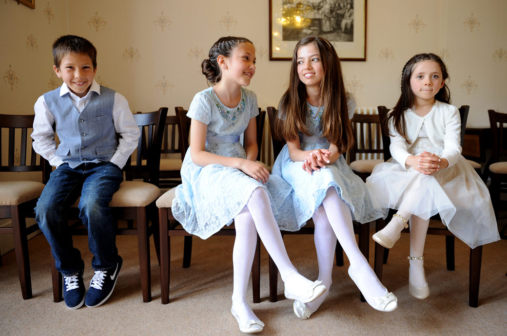Cute children sitting and waiting for mum and dad to arrive in the smaller marriage room in Artington House at Surrey wedding venue Guildford Register Office