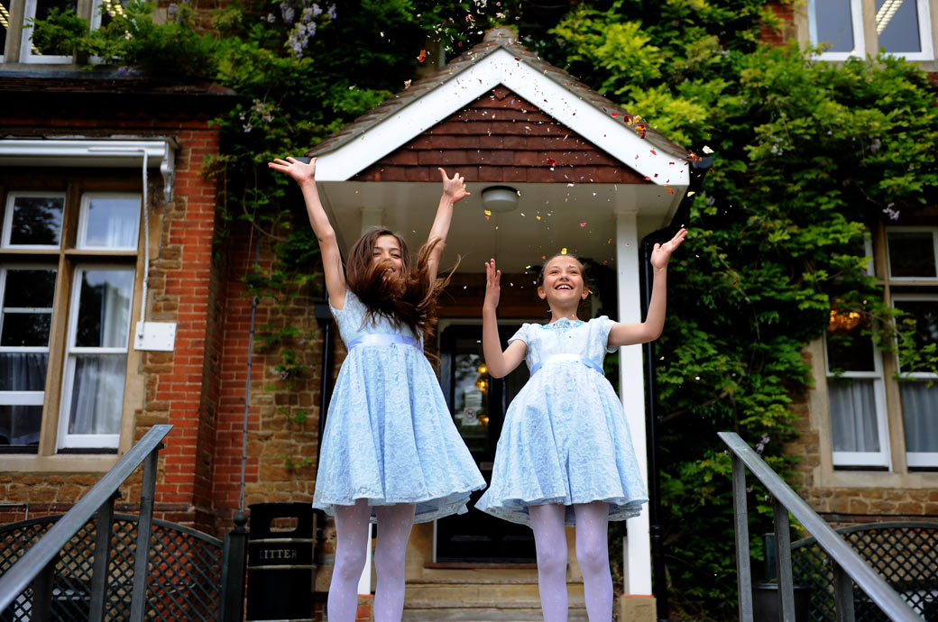 Wedding picture of little bridesmaids having fun on the steps outside Guildford Register Office in Artington House in Surrey throwing confetti on themselves