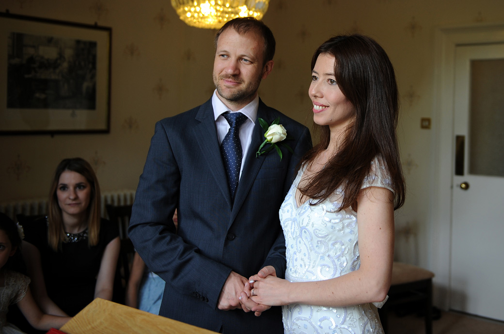 Holding hands a smiling Groom and Bride look towards the marriage registrar after completing their wedding ceremony at Artington House in Guildford Register Office Surrey