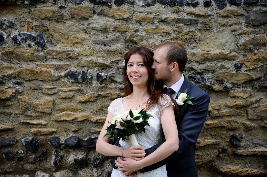 Intimate loving moment for the happy newlywed couple captured in this wedding photograph as they stand in Guildford Castle Gardens Surrey by the solid ancient walls