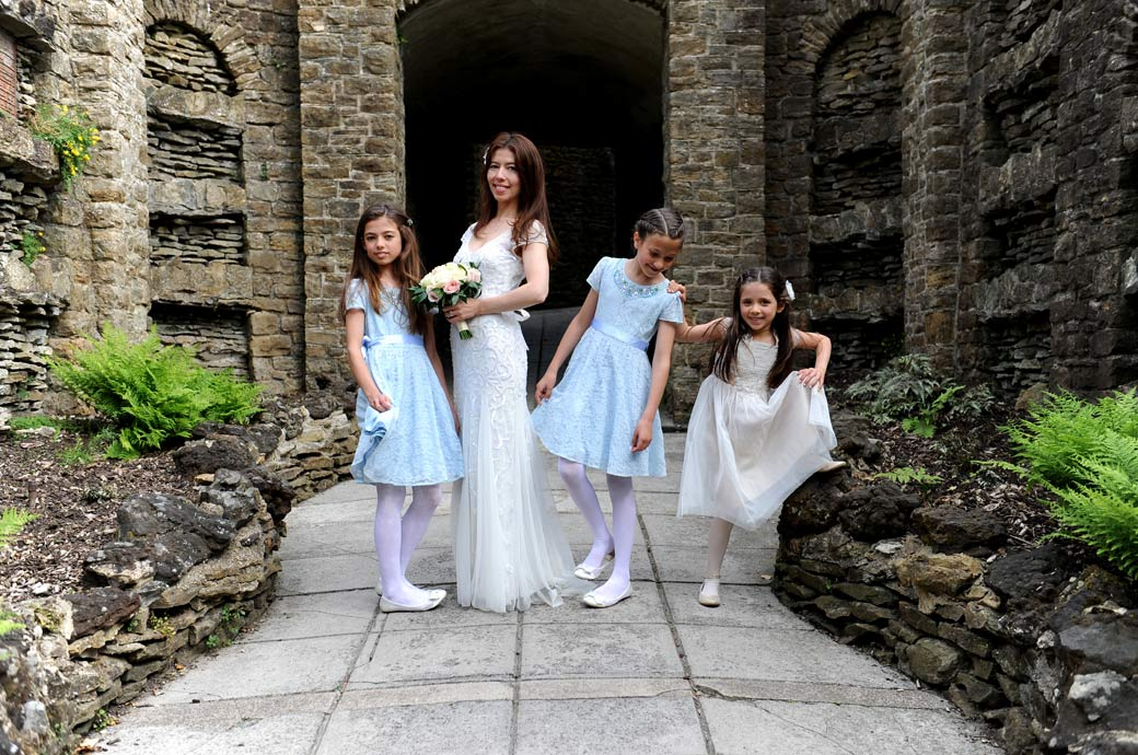 Bride poses with her cute little bridesmaids in one of the entrances of  the beautiful Guildford Castle Gardens after getting married at Guildford Register Office
