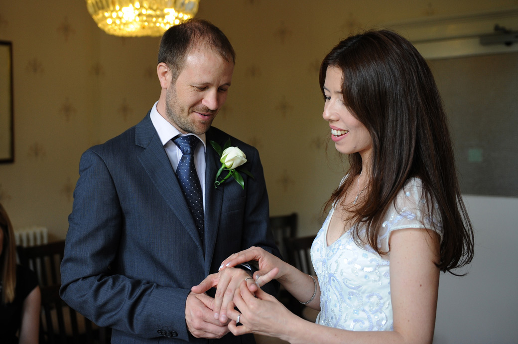 Intimate wedding picture of the bride putting the wedding ring on the Groom's  finger taken in Surrey at the popular Guildford Register Office in Artington House