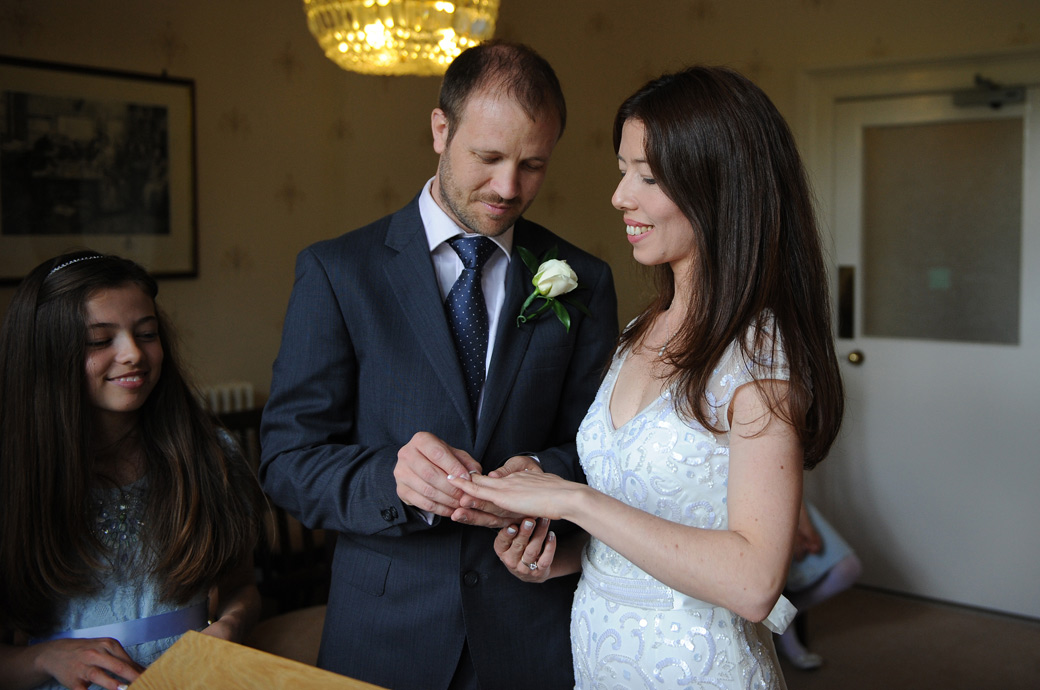 Groom places the wedding rings onto his smiling Bride's finger captured at Guildford Register Office Artington House a popular wedding venue in Surrey