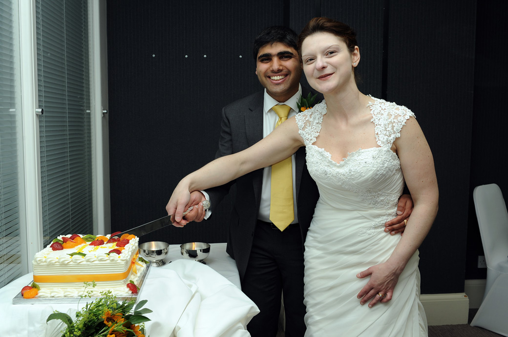 Beaming couple cutting their cake in this happy wedding photograph from Surrey wedding venue Hallmark Hotel Croydon, formerly the Aerodrome