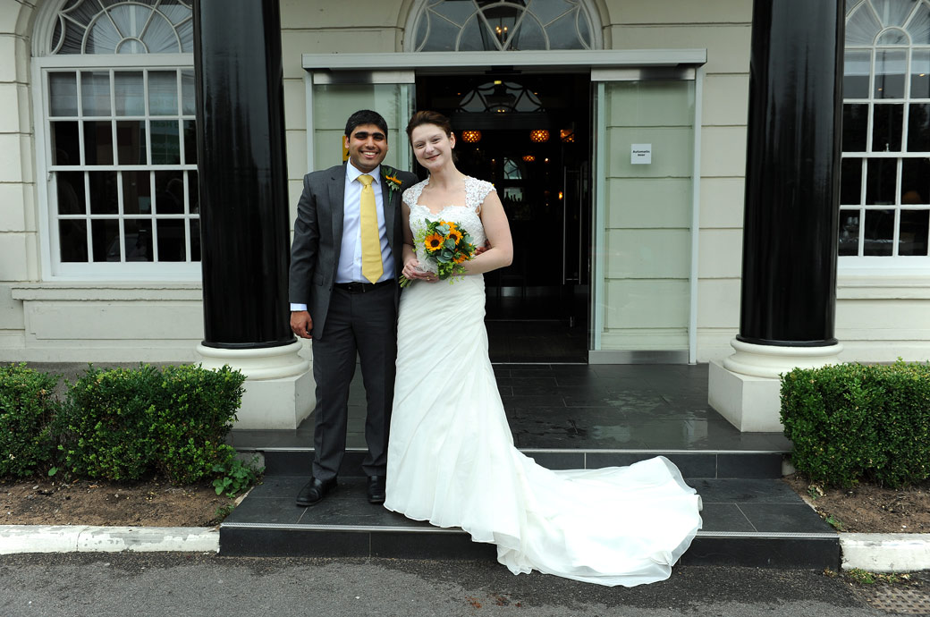 Happy smiling couple pose outside the Hallmark Hotel Croydon, formerly the Aerodrome Hotel in this relaxed Surrey wedding photograph