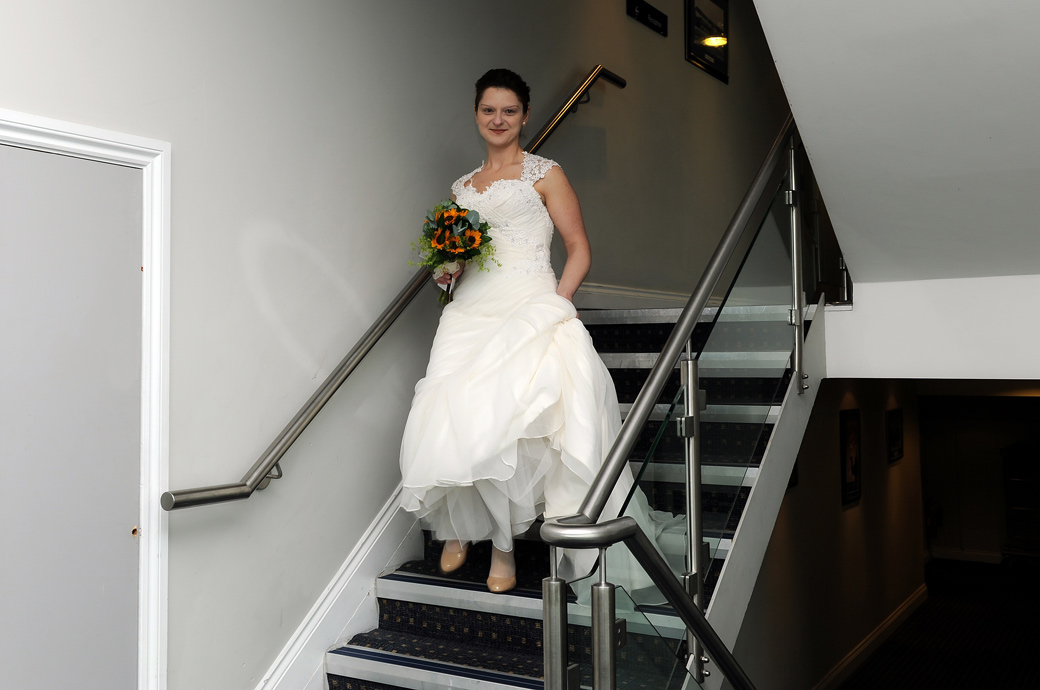 Smiling Bride descending the staircase in this lovely natural wedding picture at Surrey wedding venue Hallmark Hotel Croydon, formerly the Aerodrome Hotel