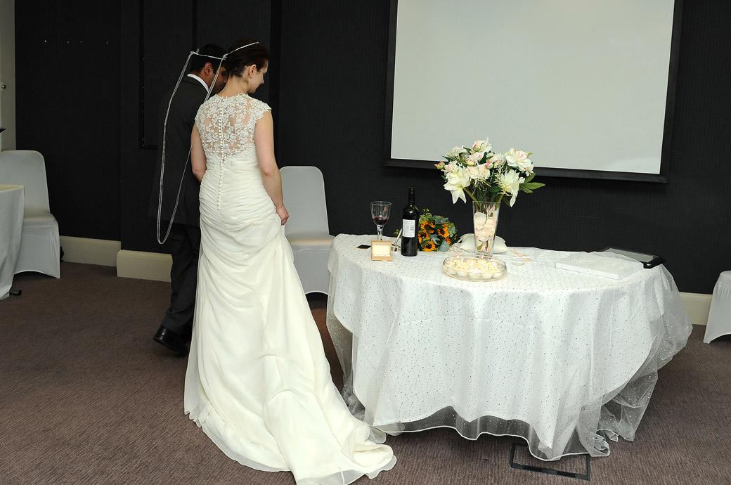 Couple joined with a white ribbon walk around table 7 times by Surrey Lane wedding photographers at the former Aerodrome Hotel now the Hallmark Hotel Croydon