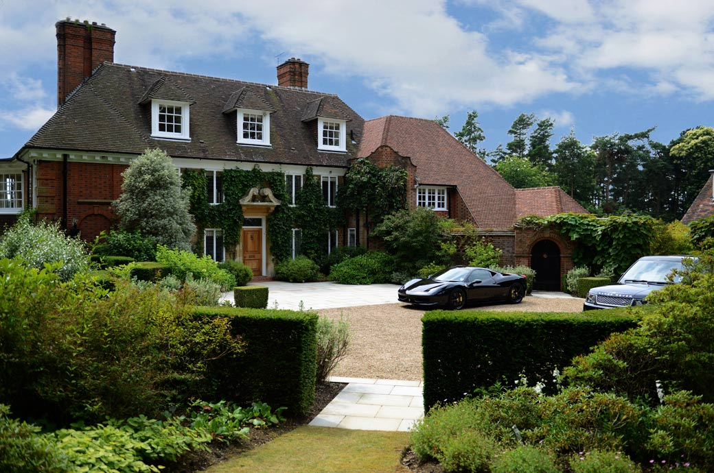 Beautiful house with Ferrari and Range Rover in the drive in this wedding photograph taken in Hindhead a stunning Surrey wedding venue