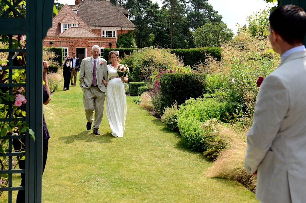 A delightful wedding picture of a smiling Bride on the arm of her father approaching the Groom for their Surrey marriage in Hindhead village