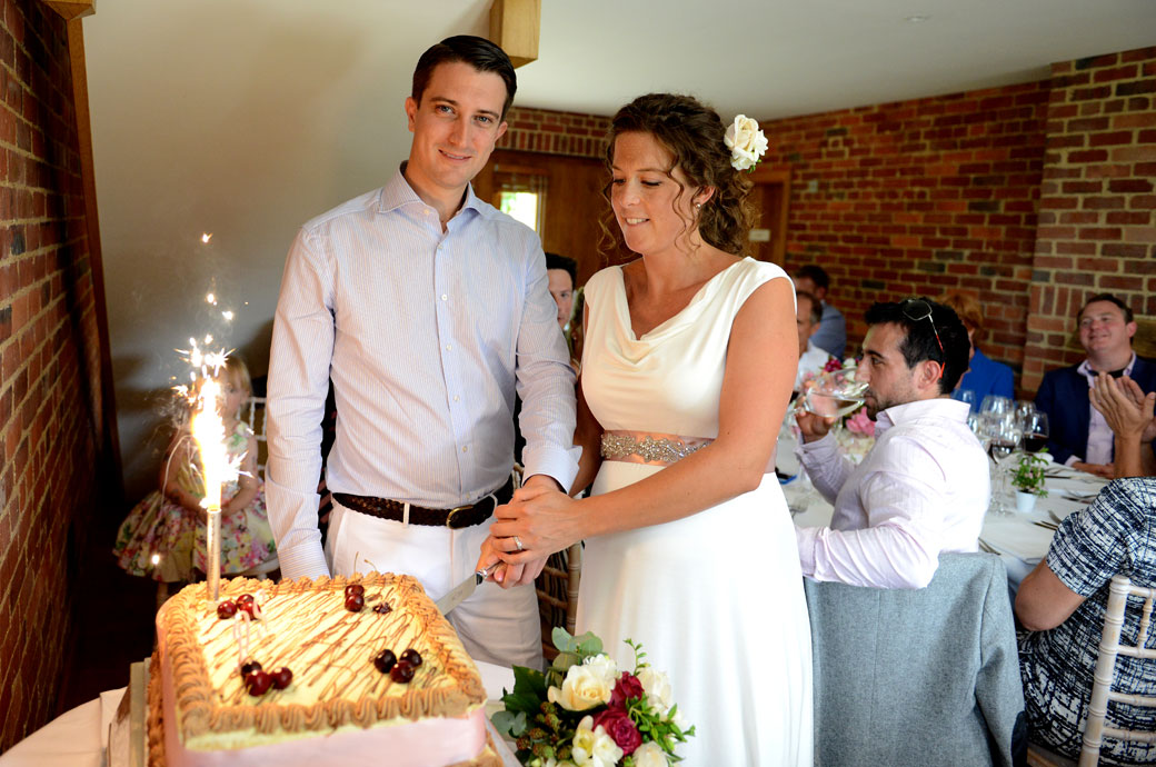Relaxed newly-weds cutting the cake in this fun wedding photograph taken at a private Surrey wedding venue in the village of Hindhead