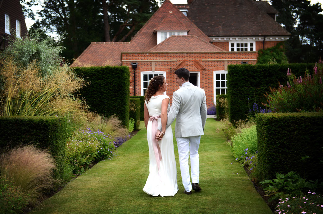 Loving looks from the newly-weds as they walk hand in hand down the lawn aisle in this delightful Surrey wedding photo taken in Hindhead village
