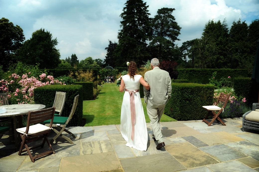 Wedding photograph taken from behind of the the Father escorting his daughter Bride down the lawn for the Surrey open air marriage ceremony in Hindhead
