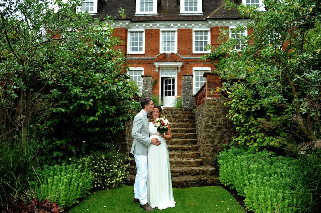 Groom kisses his wife in this lovely touching and romantic wedding picture taken in a beautiful private house garden in Hindhead Surrey