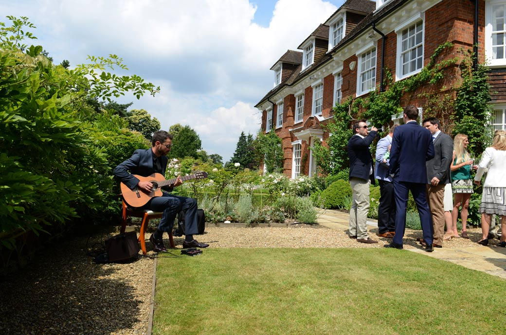 Classical guitarist providing the background music in the garden as guests chat and drink champagne in this wedding photo taken in Hindhead Surrey