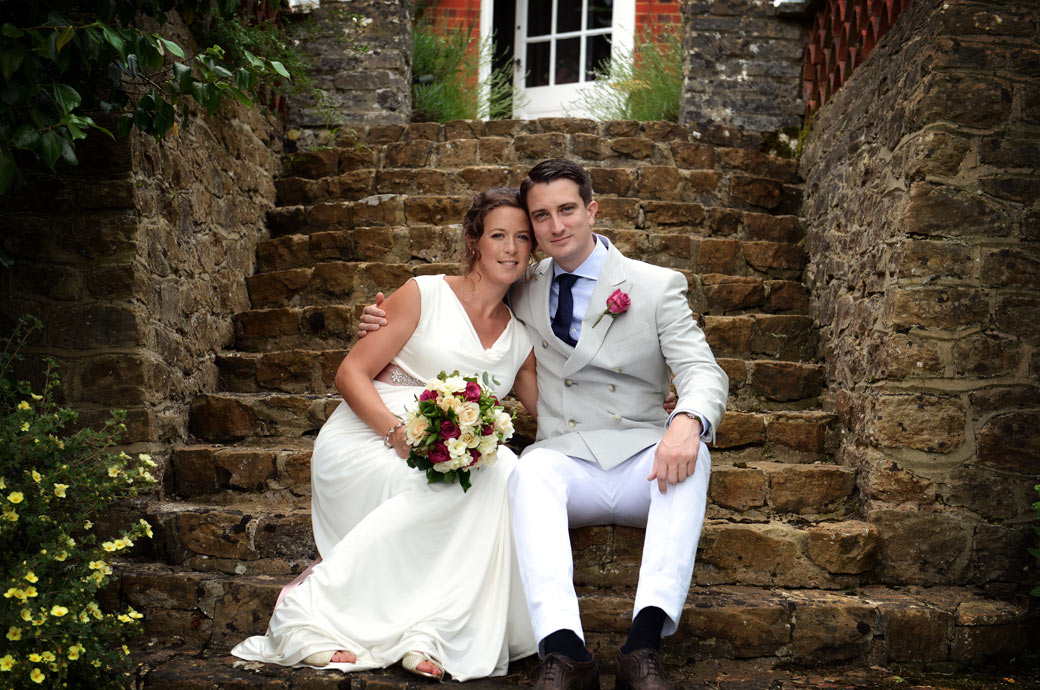 A lovely relaxed wedding photo of the happy newly-weds as they sit together on the steps of a beautiful private Hindhead Surrey wedding venue in Surrey