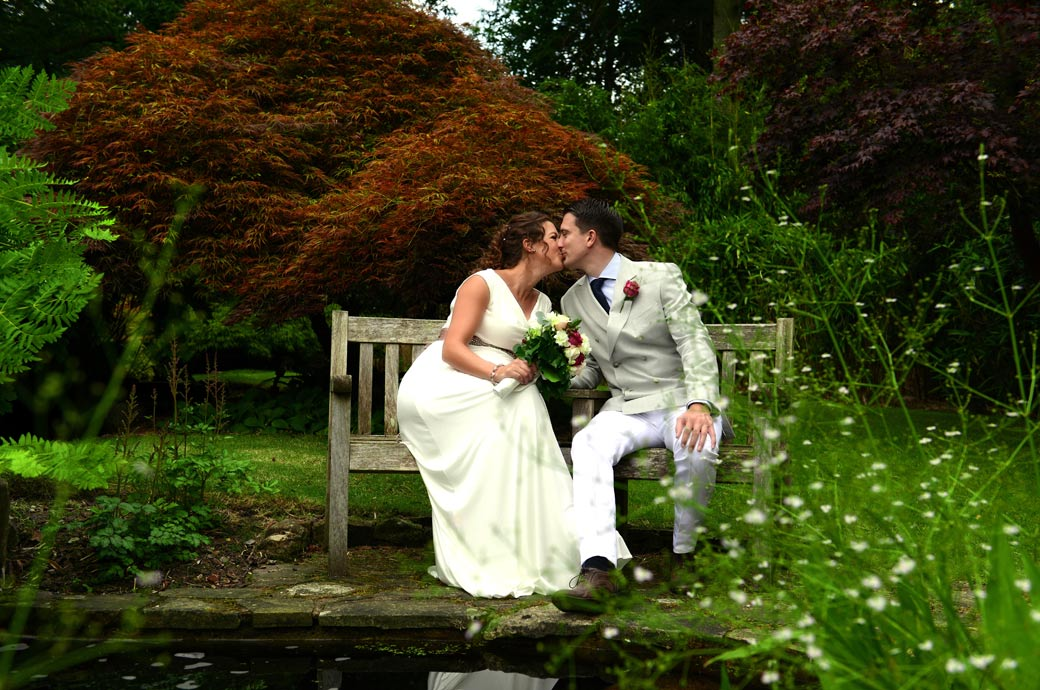 A wedding picture of newly-weds kiss as they sit on a bench in this delightful garden captured by Surrey Lane wedding photographers in Hindhead