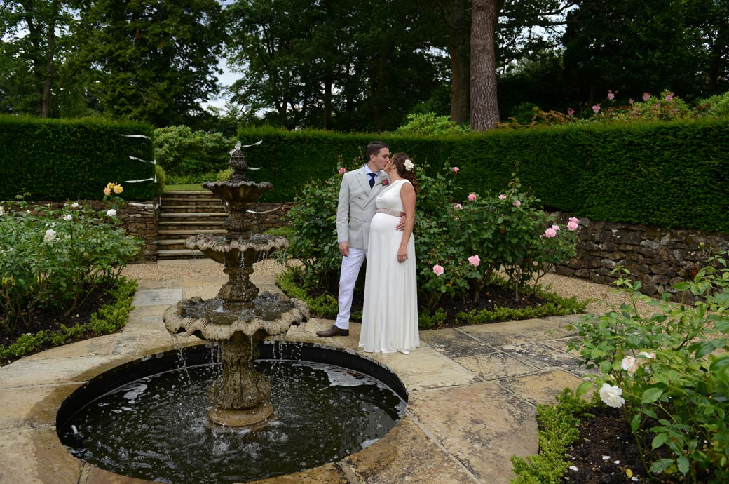 Husband and wife's romantic kiss in this wedding photo taken around the picturesque fountain in the delightful garden Surrey venue in Hindhead