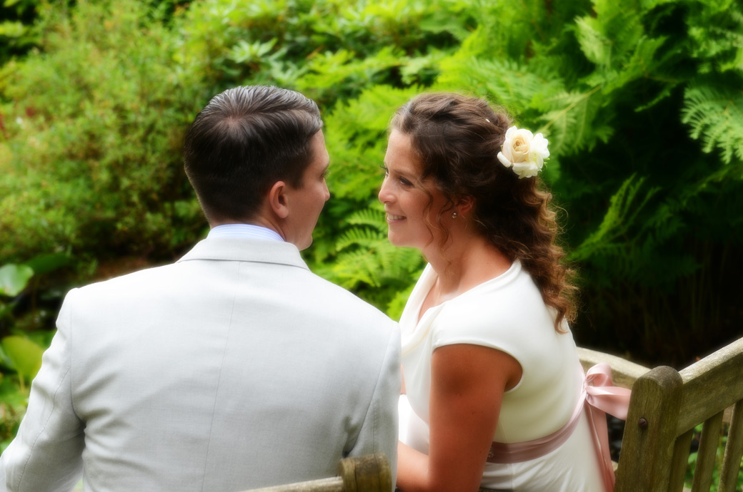 Romantic soft focus wedding photo taken of the Bride looking to her hausband as they sit on a garden seat in this private Surrey wedding venue in Hindhead