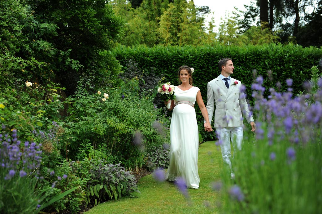 A natural relaxed wedding photograph of a happy couple taken by Surrey Lane wedding photography as they walk in this delightful garden in Hindhead village