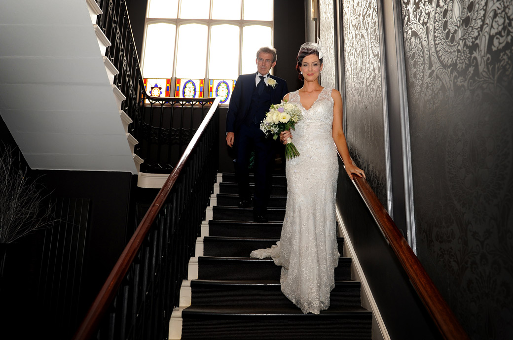 Gorgeous Bride in this wedding photo taken walking down the stairs with her father  at Surrey wedding venue Nonsuch Mansion on route to the marriage registrars for her interview