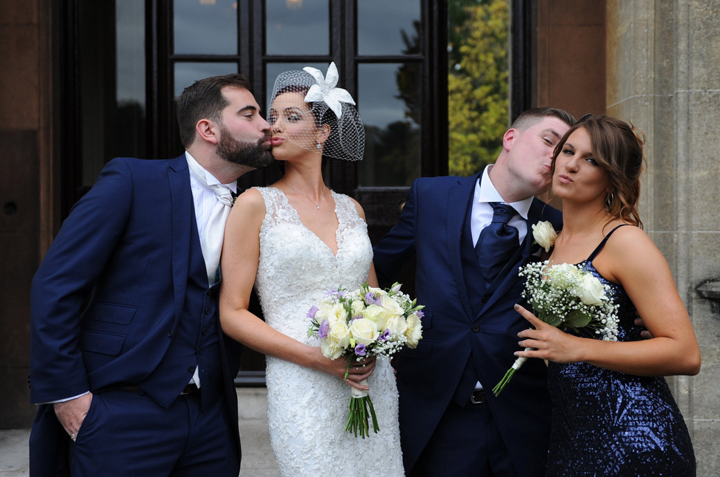 A fun pouting mock kissing wedding photograph captured at Nonsuch Mansion in Cheam village by a Surrey Lane wedding photographer