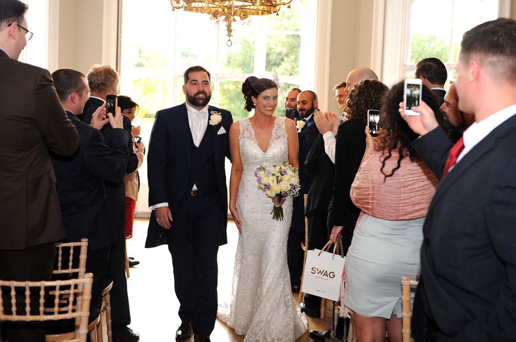 Excited and delighted Bride and Groom captured in this wedding photo walking down the aisle of the Orchid Room at Nonsuch Mansion in Cheam Surrey as husband and wife