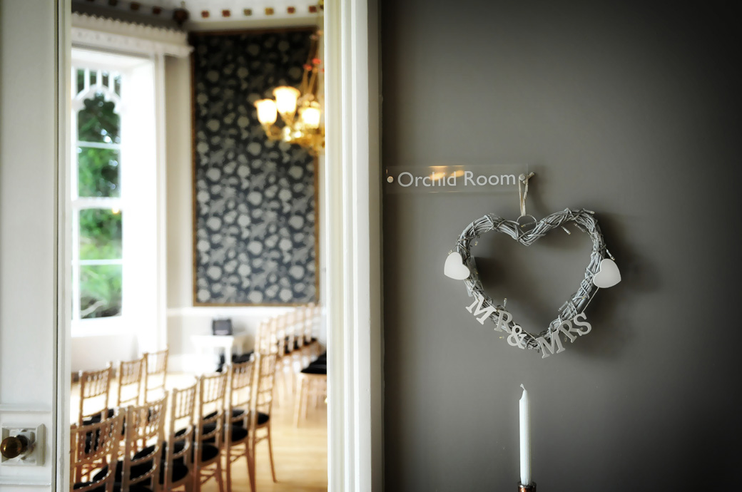 Wedding  picture of a Mr & Mrs love heart on the wall outside the open door to the Orchid Room at Surrey wedding venue Nonsuch Mansion in Cheam