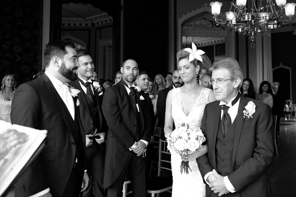 The Groom with his Best men by him smile as his lovely Bride reaches him down the aisle of the atmospheric Orchid Room at Nonsuch Mansion in Cheam Surrey