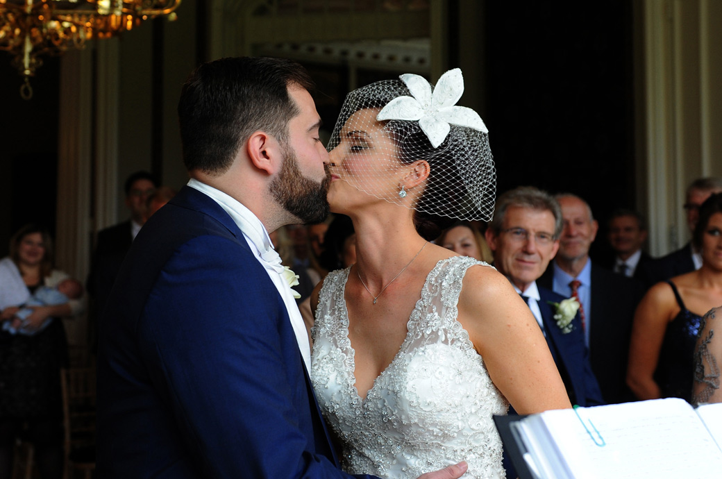 The just married couple have their first kiss as husband and wife captured in this wedding picture taken in Cheam Surrey at Nonsuch Mansion in the Orchid Room