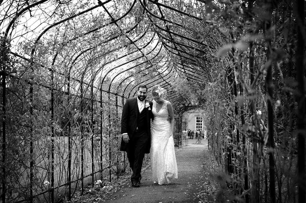 Newlyweds caught as they chat in this romantic wedding photograph taken at Surrey wedding venue Nonsuch Mansion as they walk arm in arm in the rose walk