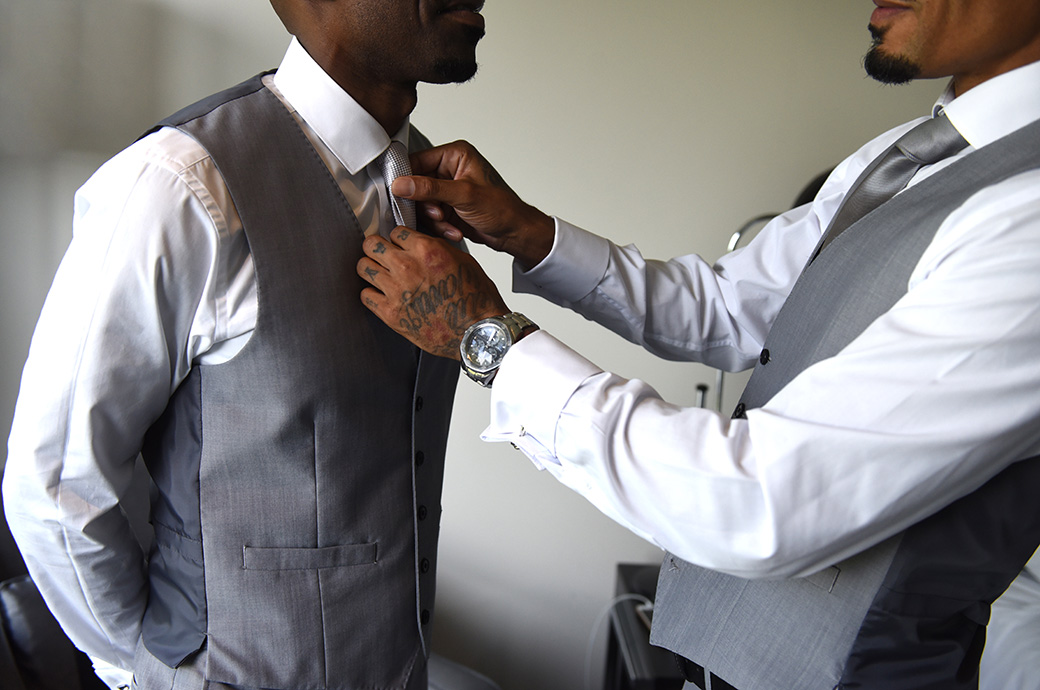 Close up wedding picture of the best man straightening the Groom's tie at the Brooklands Hotel before a Church ceremony and Painshill Park reception