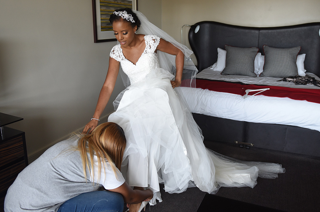 Beautiful Bride helped on with her shoes at the Brooklands Hotel before leaving for her church wedding in Cobham and Painshill Park reception