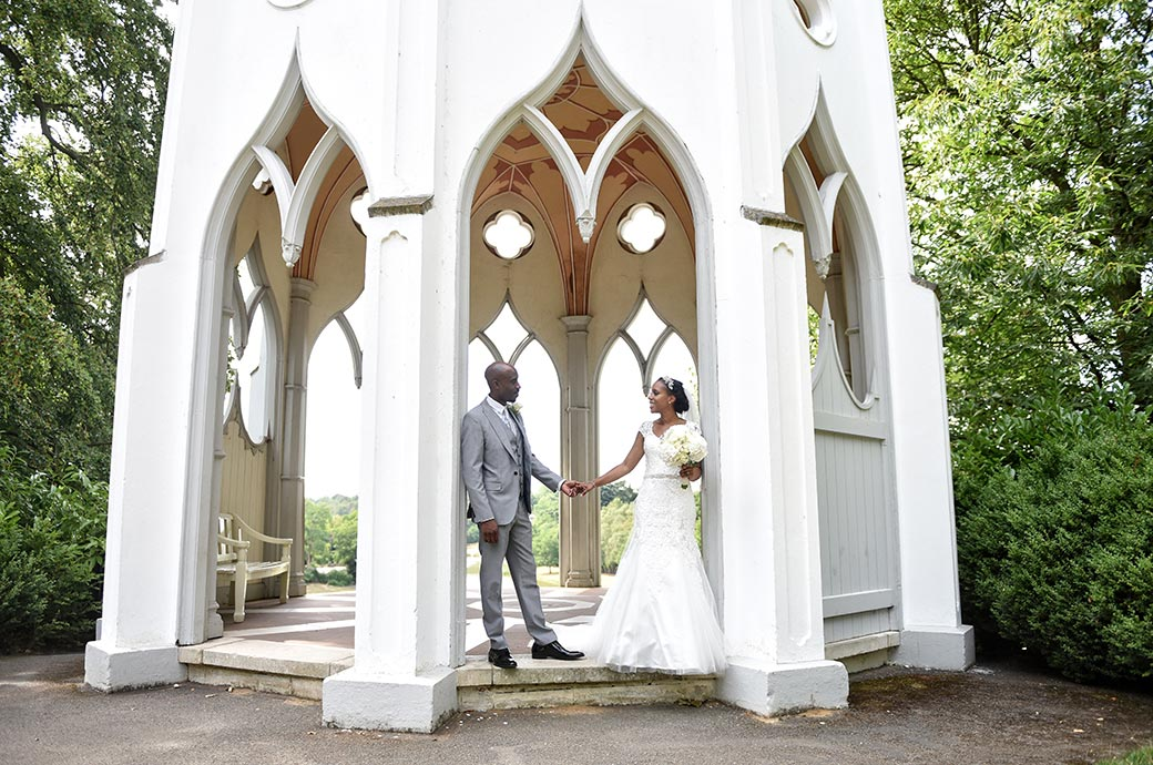 Romantic wedding couple holding hands at Surrey venue Painshill Park as they stand in the arch of the wonderful Gothic Temple