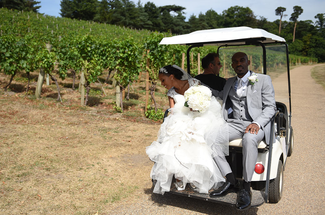 Relaxed looking bride and groom sitting on the back of a golf buggy as they pass the Painshill Park vineyard after a romantic trip around this scenic Surrey wedding venue