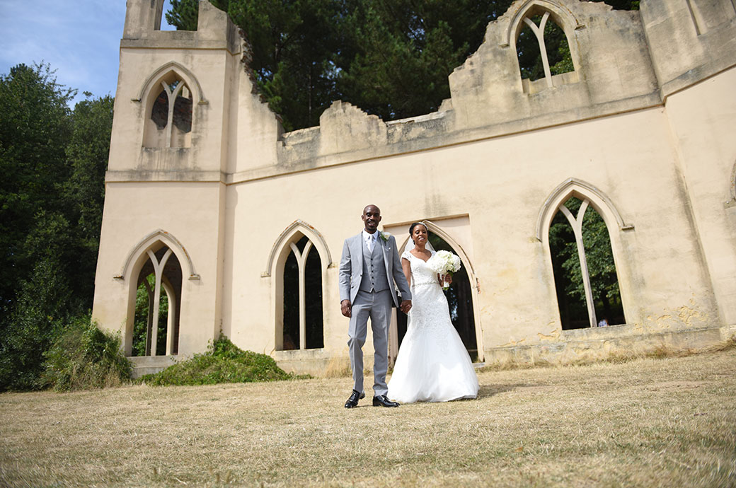 Happy smiling newlywed couple walking along the grass from the Ruined Abbey at Surrey wedding venue Painshill Park in Cobham