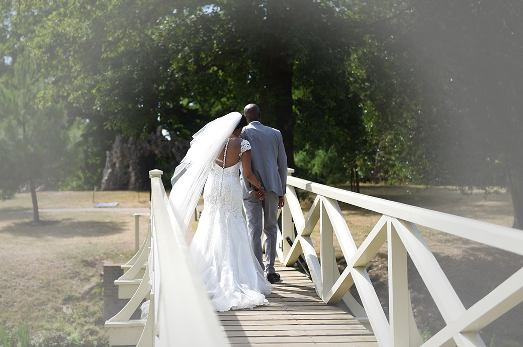 Relaxed wedding picture of a Bride and Groom at Surrey wedding venue Painshill Park taken as they walk across the white wooden Chinese Bridge