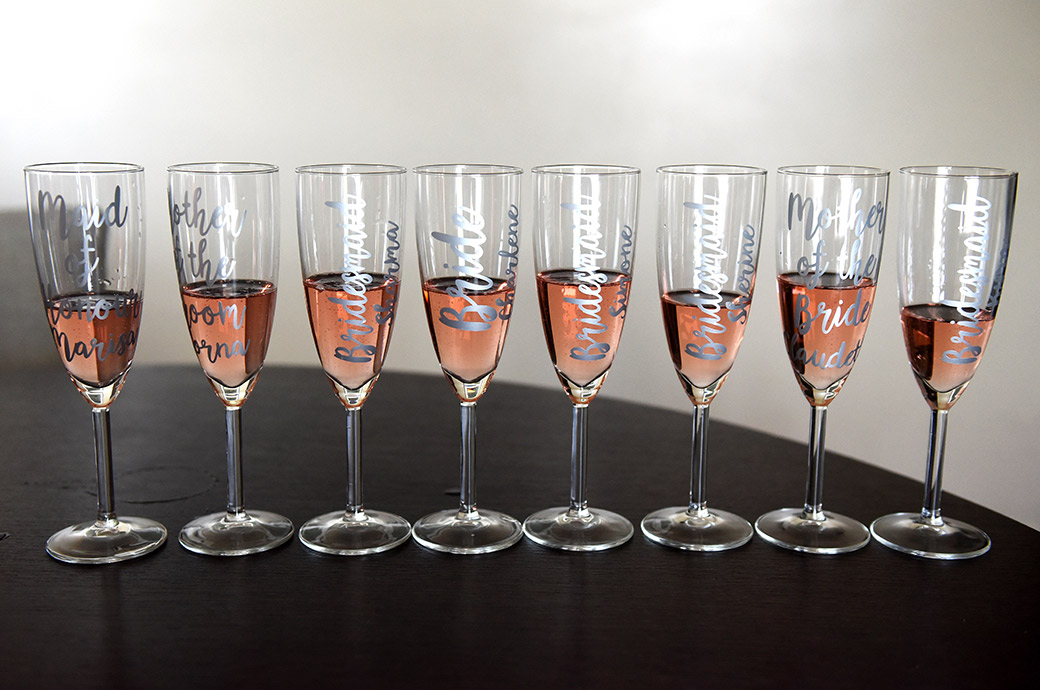Eight personalised glasses of pink champagne lined up for the Bride and her ladies at the Brooklands Hotel before a church wedding and reception at Painshill Park Cobham Surrey