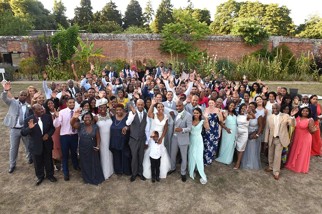 Everyone at the wedding at Painshill Park Surrey waving at the photographer outside the  Conservatory in the colourful and private Walled Garden